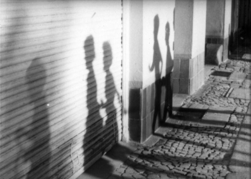 Schwarz-Weiß-Szenenfoto: Schatten an einer Wand