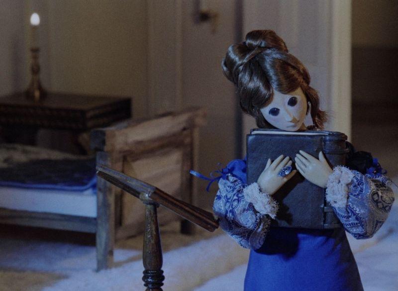 Ein Puppenmädchen drückt ein Buch an sich, aus dem Trickfilm Die Schöne und das Tier