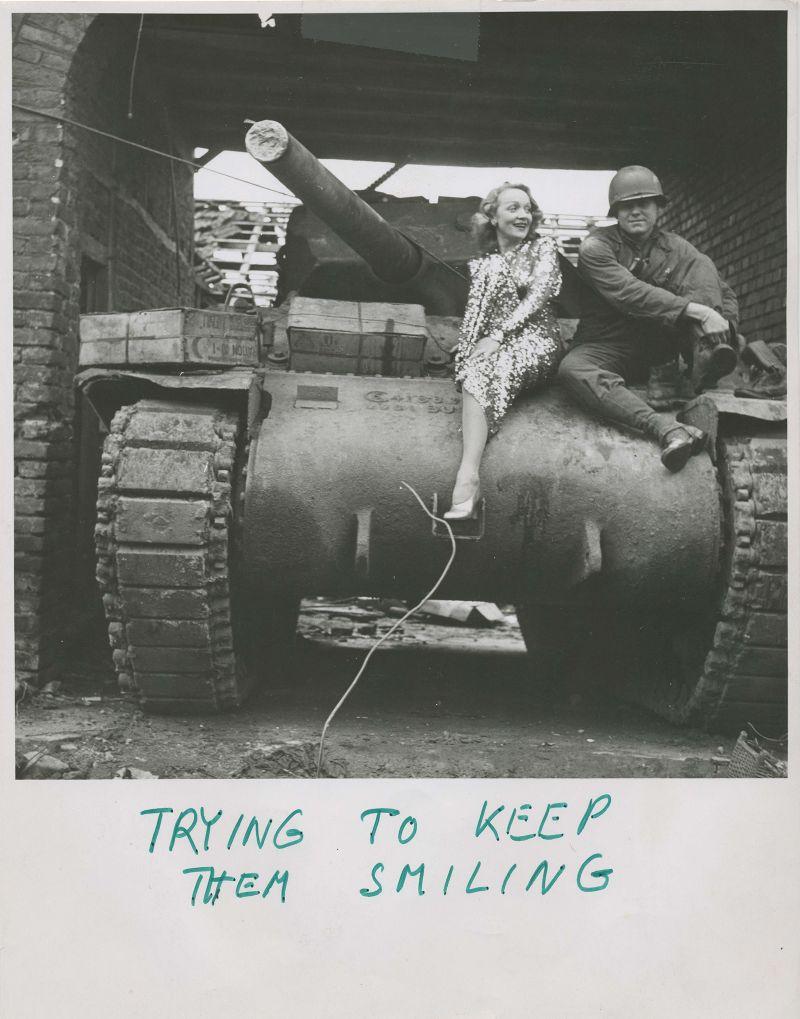 Marlene Dietrich im Auftrittskostüm auf einem Panzer der US-Amerikanischen Streitkräfte