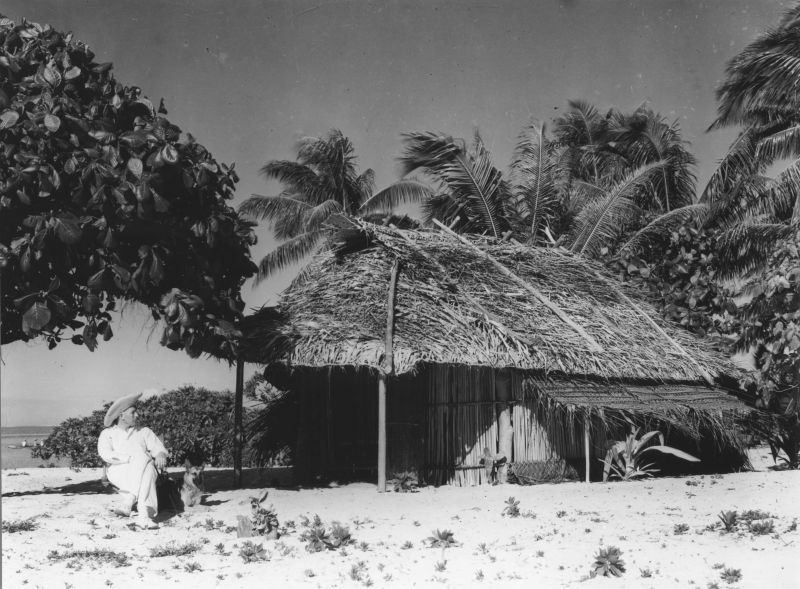 Black and white photo taken on the beach in front of a thatch roof hut