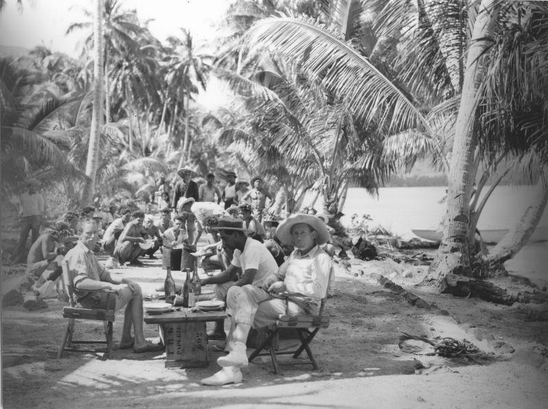 Schwarz-Weiß-Foto: Männer sitzen an einer Holzbank am Strand