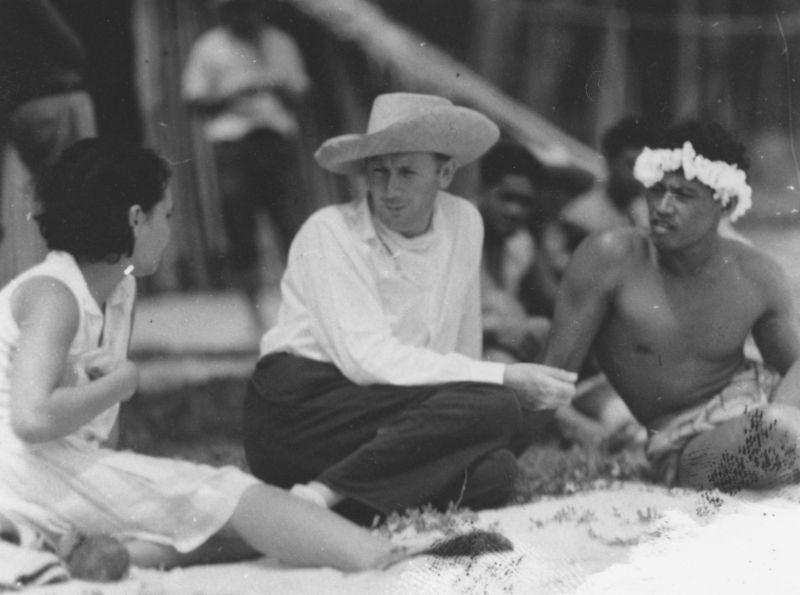 Schwarz-Weiß-Foto: Drei Menschen sitzen redend am Strand