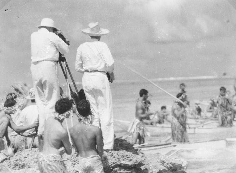 Schwarz-Weiß-Foto: Flaherty und Murnau an der Kamera am Strand, im Hintergrund Einheimische beim Fischen im Meer