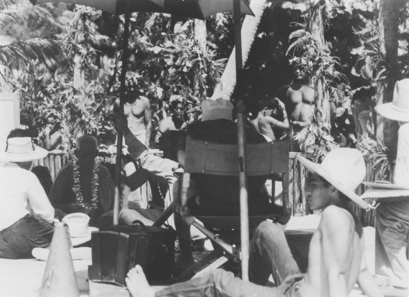 Black and white photo on set showing many people out in nature