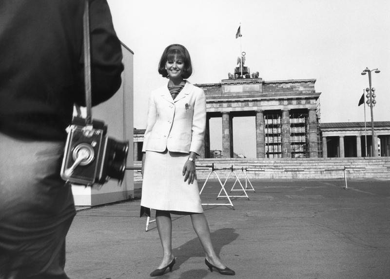 Claudia Cardinale mit einem Fotografen vor dem Brandenburger Tor,1964