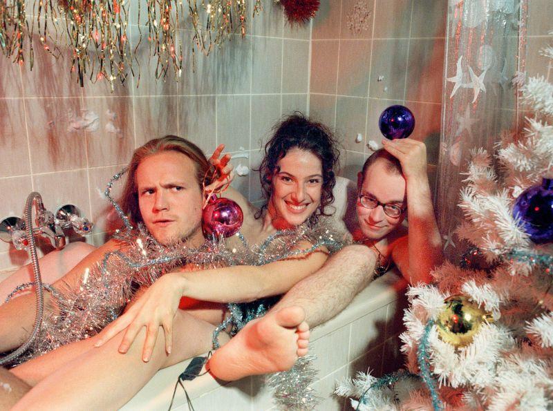 Klaus Beimer, Suzanne Richter und Philipp Sperling nackt in einer Badewanne, die weihnachtlich dekoriert ist.