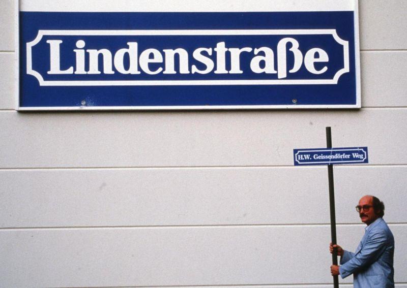 Geissendörfer mit einem Schild Lindenstraße unter dem großen Straßenschild Lindenstraße