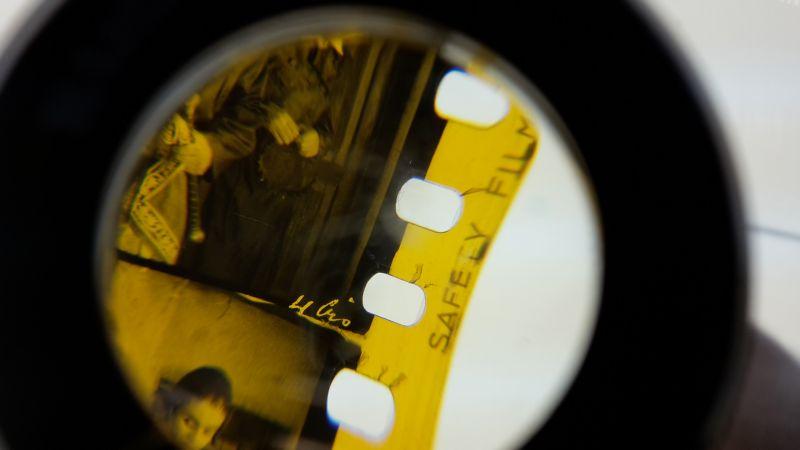 Ein Filmstreifen unter einer Lupe. Man sieht, dass die Perforation des Filmstreifens eingerissen ist.