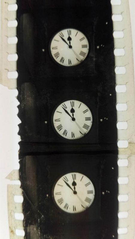 Ein Stück eines Filmstreifens mit drei Bildern auf denen eine Uhr mit der Uhrzeit 11:55 Uhr zu sehen ist.