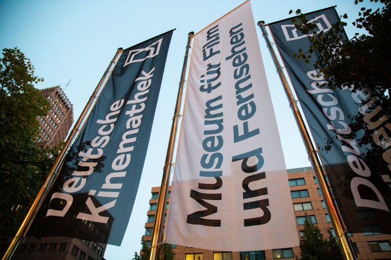 """Flags with the logo """"Deutsche Kinemathek – Museum für Film und Fernsehen"""" infront of the Filmhaus"""