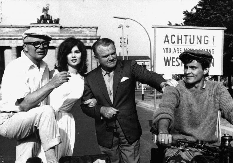 Regisseur Billy Wilder mit Schauspieler*innen vor dem Brandenburger Tor