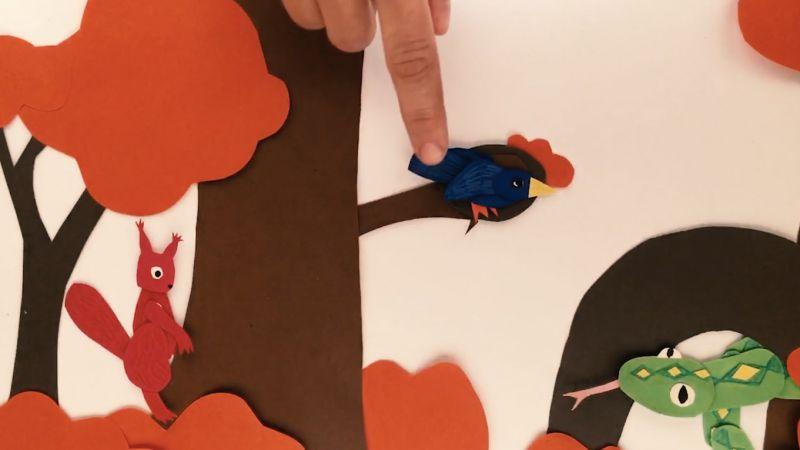 Ausgeschnittene Papierfiguren (Schlange, Eichhörnchen, Vogel) werden von einer Hand zurechtgelegt