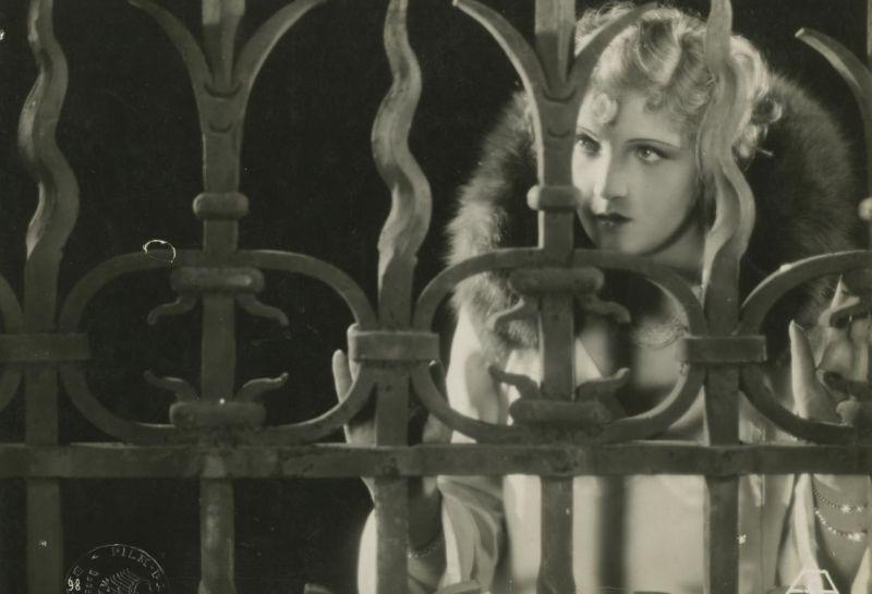 Frau im Pelzmantel steht hinter Gittertor