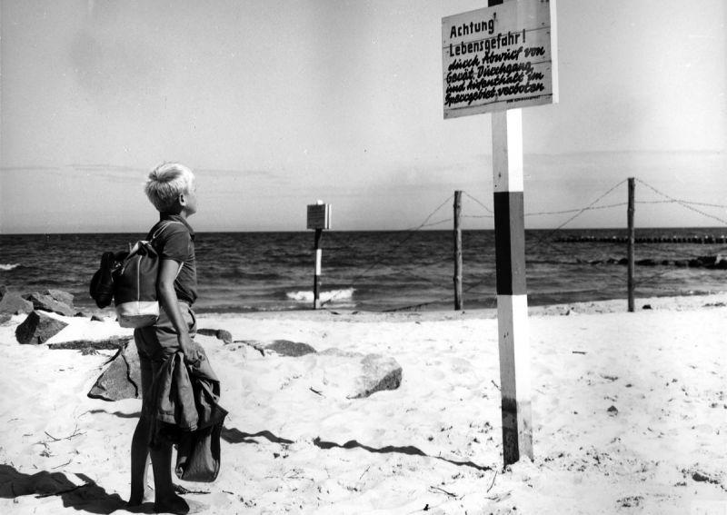 Kleiner Junge am Strand vor einem Schild Achtung Lebensgefahr