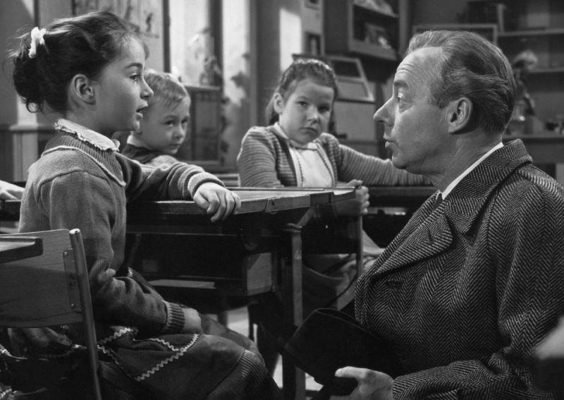 Heinz Rühmann knieend vor drei Kindern in der Schulbank