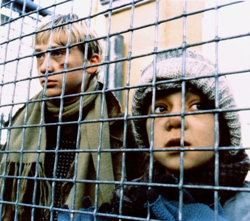 Farbbild. Zwei Jungen stehen hinter einem Gitterzaun und schauen hindurch. Sie tragen Schal und Mütze und sehen müde aus. Der Junge links hat eine Wunde im Gesicht.
