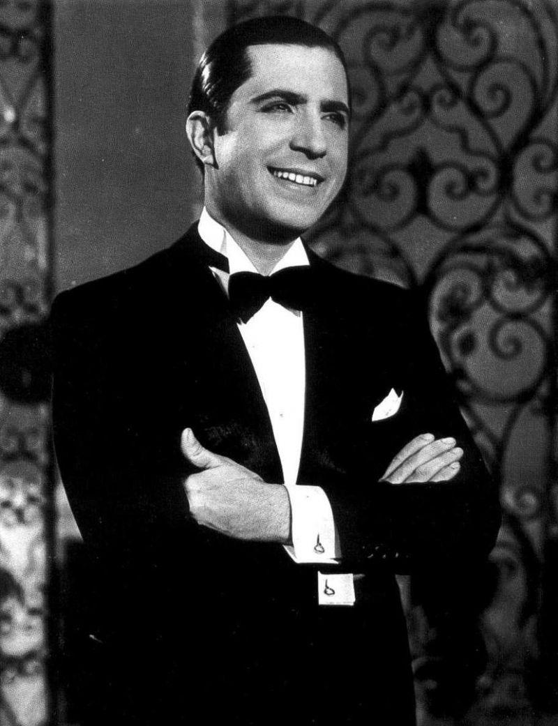 Schwarz-weiß Bild. Ein Mann in einem Smoking mit Fliege, der lächelt und die Arme verschränkt. Es ist der argentinische Tango-Sänger Carlos Gardel.