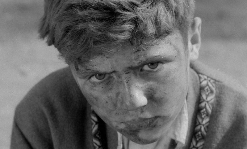 Schwarz-weiß Bild. Großaufnahme eines Gesichts: ein Junge schaut trotzig in die Kamera; sein Gesicht ist schmutzig.