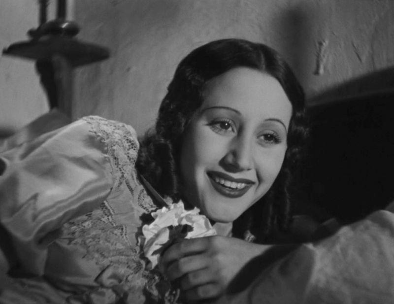 Schwerz-weiß Bild, eine junge Frau in einem Spitzenkleid liegt auf einem Bett und lächelt