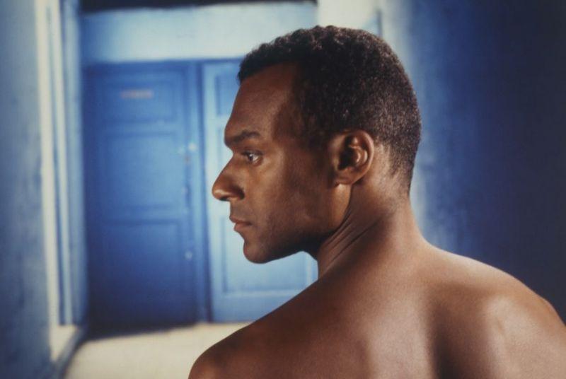 Filmstill mit Colin Salmon als Frantz Fanon: ein Mann von hinten mit nackten Schultern und zur Seite gedrehten Kopf vor blauem Hintergrund.