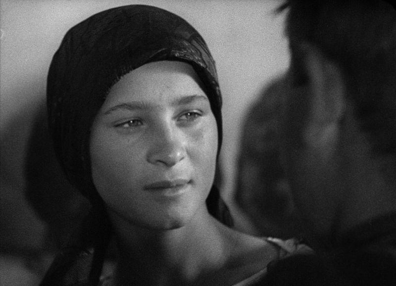 Schwarz-weiß Bild. Das Gesicht einer jungen Frau, einer Bäuerin, mit einem Kopftuch. Sie blickt einen Mann an, den man nur von hinten sieht.