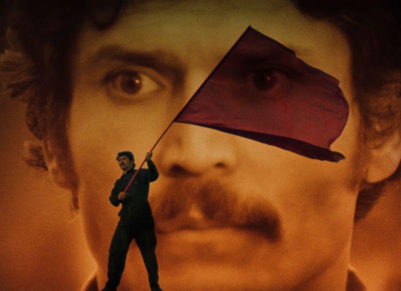 Filmbild in Orange- und Rottönen. Ein Mann schwenkt eine rote Fahne vor einer Wand; das Gesicht eines Mannes ist auf die Wand projiziert.