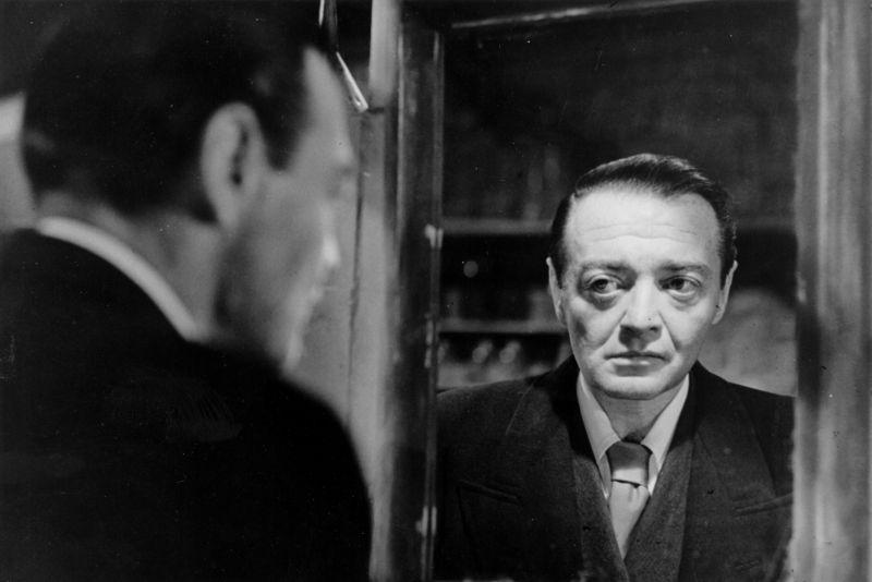 Schwarz-weiß Bild. Ein älterer Mann im Anzug sieht sich selbst ernst in einem Spiegel an. Man sieht sowohl ihn von hinten als auch sein Spiegelbild.
