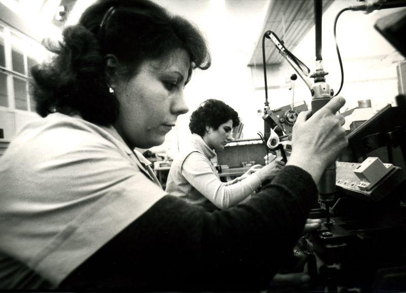 Schwarz-weiß Bild. Zwei Frauen sitzen in Arbeitskitteln an Maschinen in einer Fabrik.