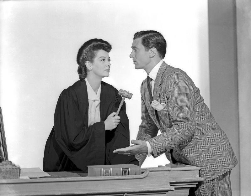 Schwarz-weiß-Szenenfoto: Rosalind Russel in Richterrobe mit einem jungen Mann