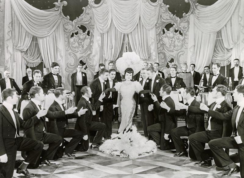 Schwarz-weiß-Szenenfoto: Mae West in pompöser Robe, um sie herum knieende Männer
