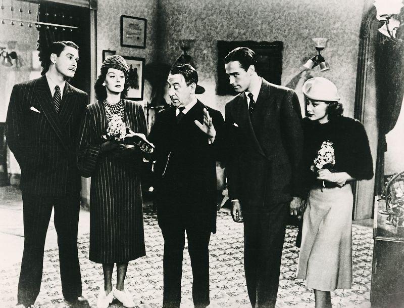 Schwarz-weiß-Szenenfoto: zwei Frauen und zwei Männer hören einem Mann mit Buch in der Hand zu