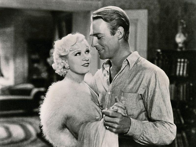 Schwarz-weiß-Szenenfoto: Mae West und Randolph Scott halten sich zärtlich an den Händen