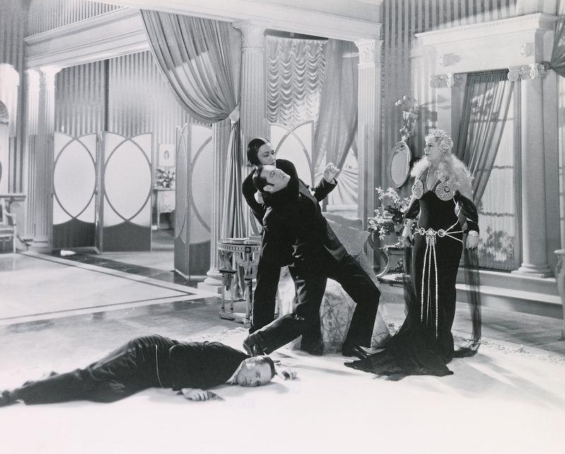 Schwarz-weiß-Szenenfoto: Dramatische Szene einer Handgreiflichkeit, ein Mann mit Pistole liegt am Boden