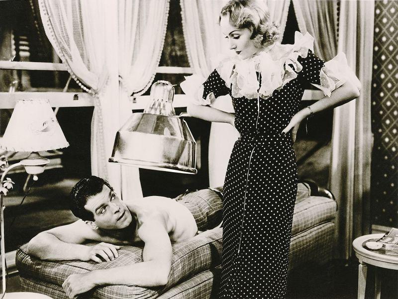 Schwarz-weiß-Szenenfoto: Frau stehd neben Mann am Massagetisch