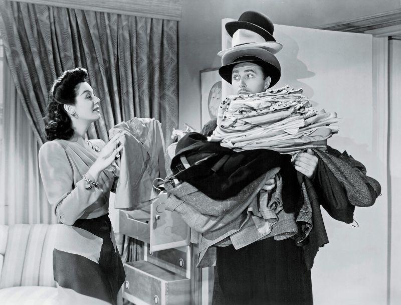 Schwarz-weiß-Szenenfoto: Frau lädt einem Mann einen Riesenberg Wäsche auf die Arme