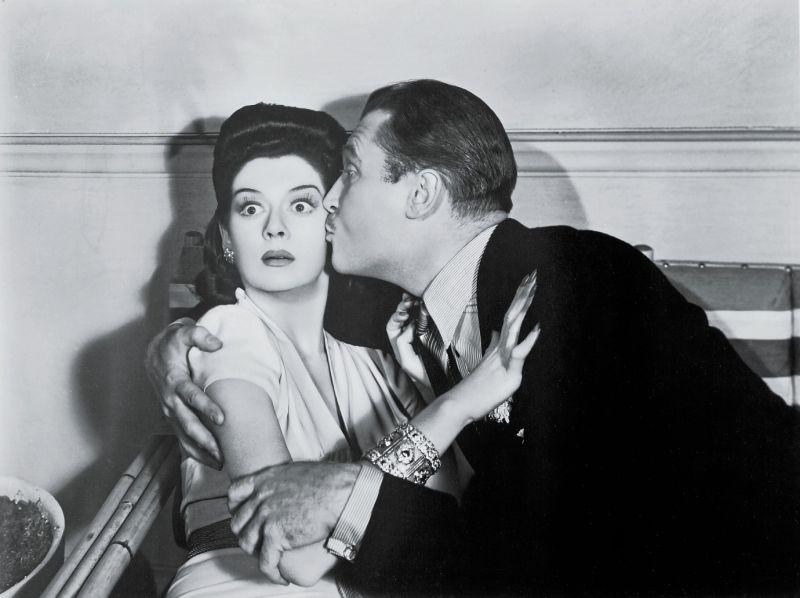 Schwarz-weiß-Szenenfoto: Mann gibt einer überrascht guckenden Frau einen Kuss auf die Backe