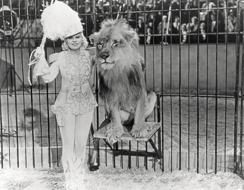 Szenenfoto einer Frau in glitzerndem Kostüm, die mit einem Löwen posiert.