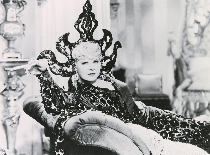 Schwarz-weiß-Szenenfoto: Elegante Frau in extravagantem Kleid liegt auf einer Chaiselonge und raucht