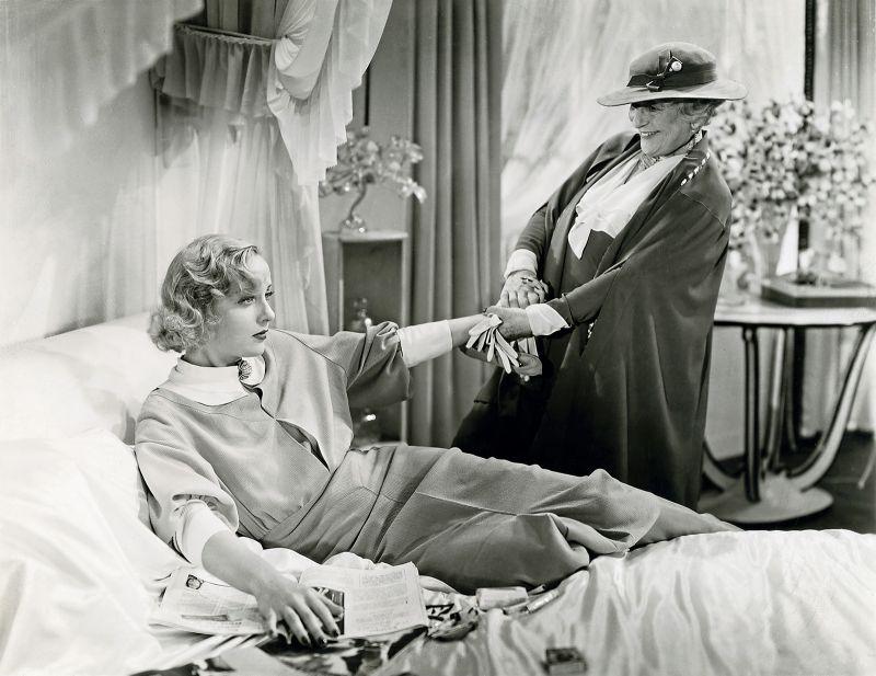 Schwarz-weiß-Szenenfoto: Ältere Frau besucht junge Frau, die im Bett liegt