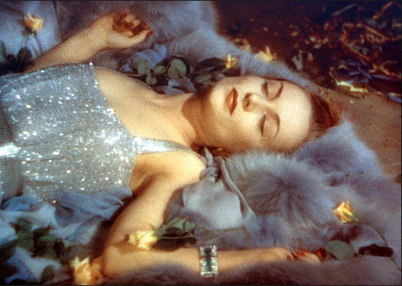 Farbiges Szenenfoto: Frau in elegantem Kleid liegt