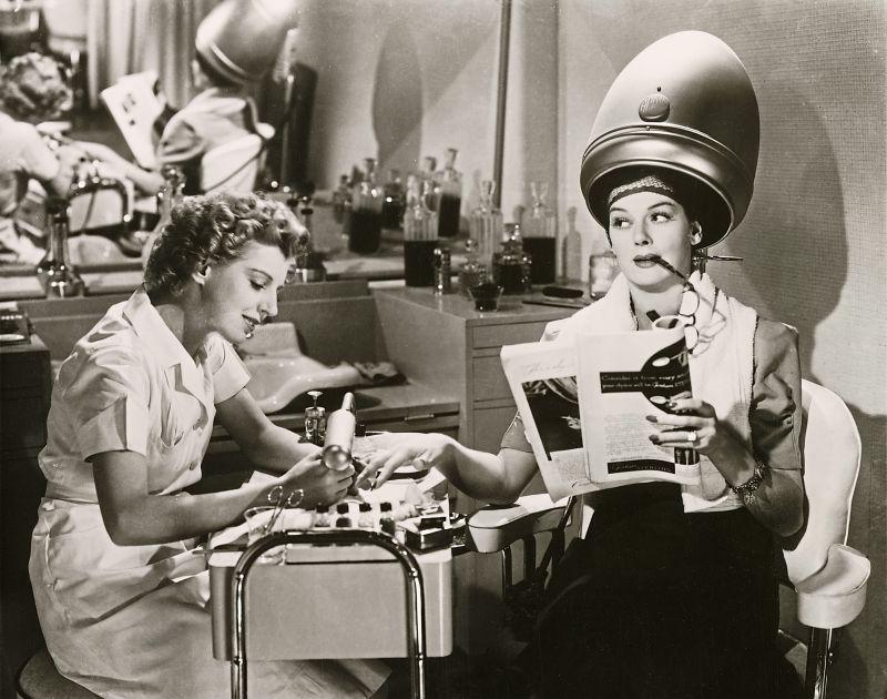 Schwarz-weiß-Szenenfoto: Eine Frau sitzt unter der Trockenhaube und bekommt eine Maniküre