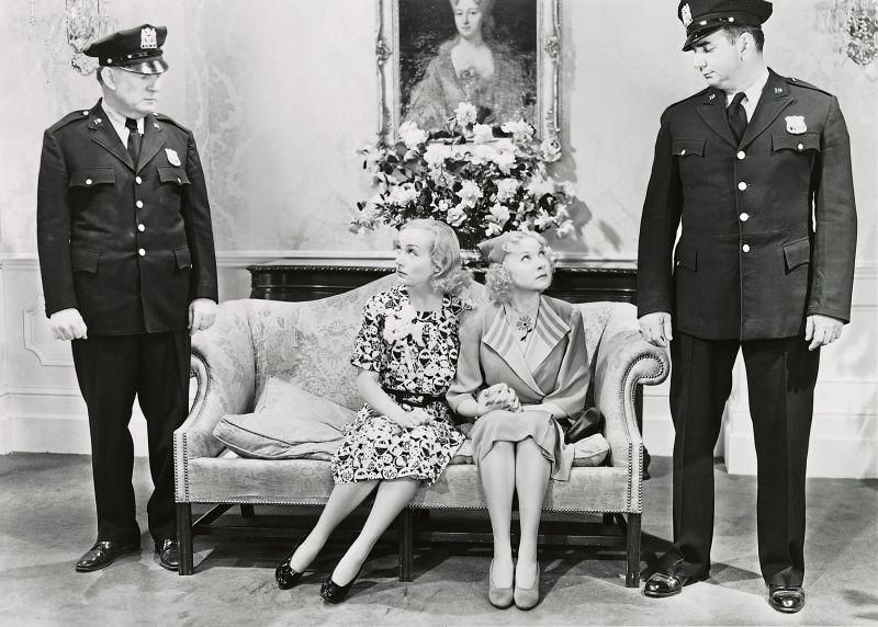 Schwarz-weiß-Szenenfoto: Zwei Frauen sitzen auf einem Sofa, neben ihnen zwei Polizisten