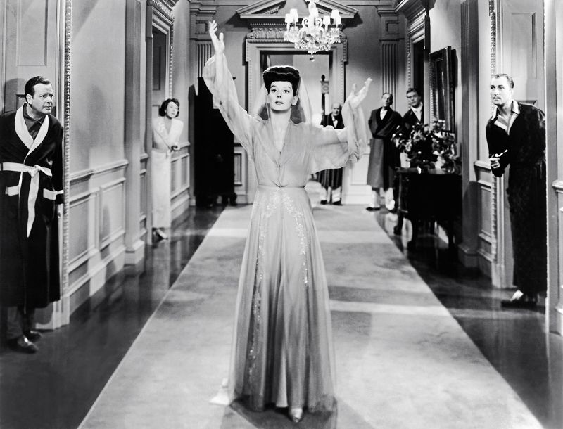 Schwarz-weiß-Szenenfoto: Frau in elegantem Morgenmantel läuft durch Hotelgang