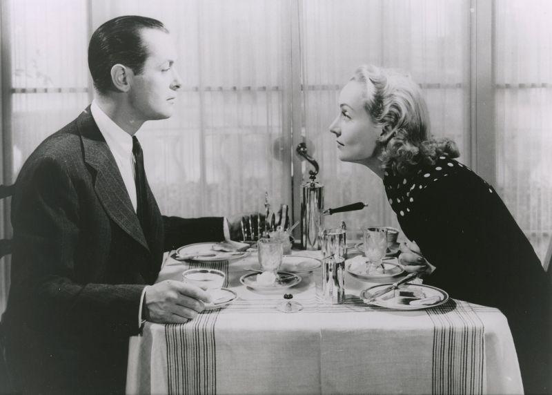 Schwarz-weiß-Szenenfoto: Mann und Frau sitzen sich am Esstisch gegenüber