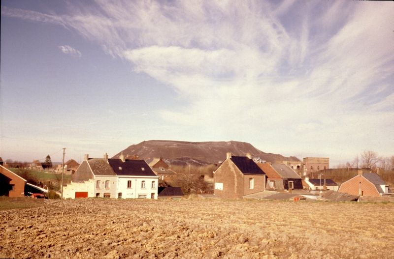 A field with houses and in the background a boulder-mountain
