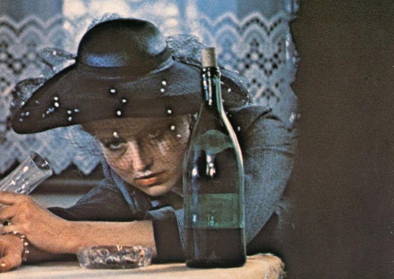 Hanna Schygulla am Tisch liegend mit einer Flasche