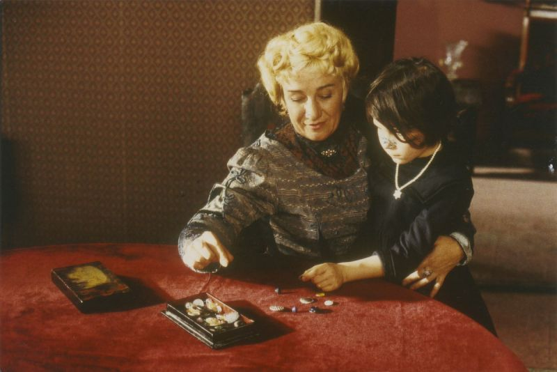 Film still, an elderly woman plays with a child