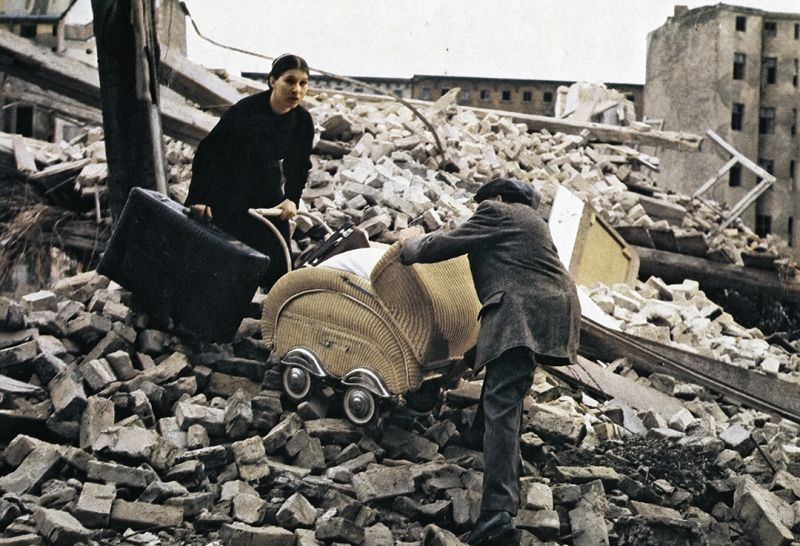 Still of a woman and man carrying a pram over rubble
