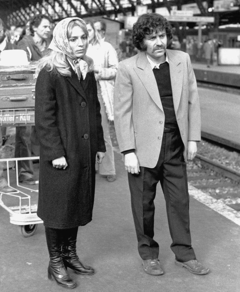 Szenenfoto von einem Mann und einer Frau an einem Bahnhof
