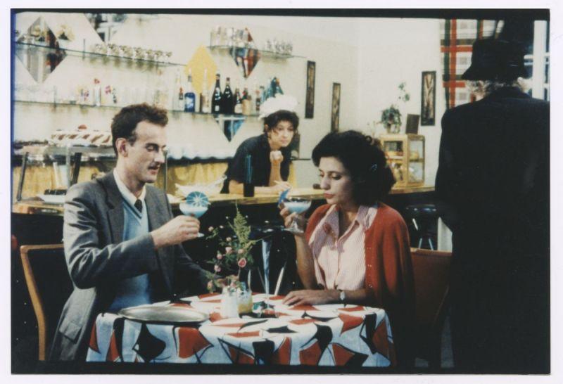 Szenenfoto in Farbe von einem Mann und einer Frau an einem Tisch sitzend